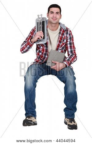 Man with tile cutter sat on ledge
