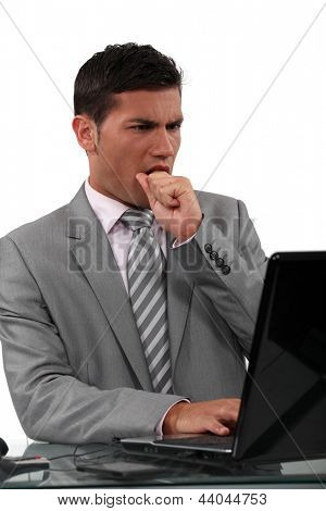 businessman looking at his laptop and eating his fist