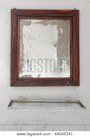 Mirror in a dilapidated white bathroom