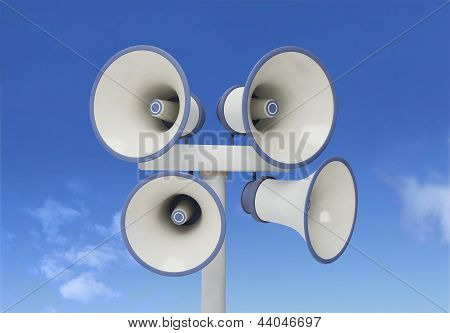 Four megaphones on the pole on sky background