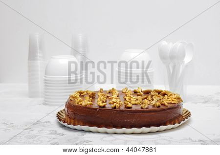 chocolate cake with nuts on a table with a white tablecloth and white cups and bowls