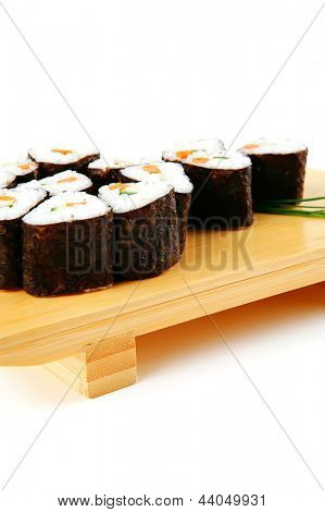 sushi rolls with green stems on wood stand