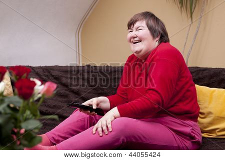 Mentally Disabled Woman Watching Television And Enjoys