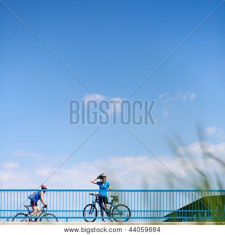 Background for poster or advertisment pertaining to cycling/sport/outdoor activities - female cyclist during a halt on a bridge against blue sky (color toned image)