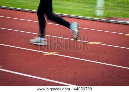 Young woman running at a track and field stadium (motion blurred image)