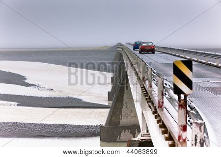 Two Cars At A Bridge Under Muddy River In Iceland.