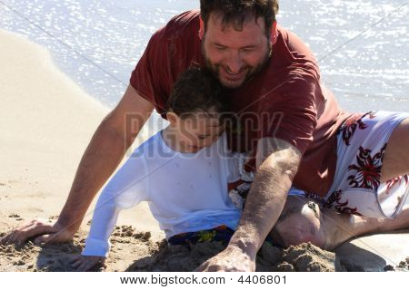 Father And Son Playing In The Sand Together