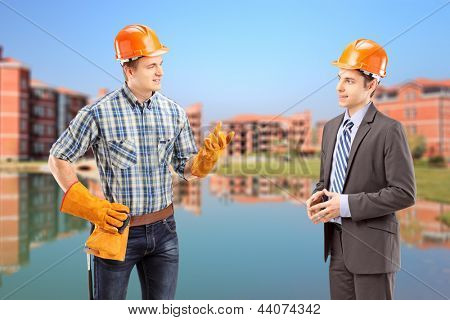 A male manual worker having a conversation with architect, construction site in the background