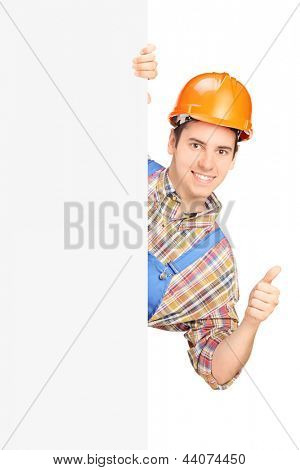 Young construction worker with helmet posing behind a panel and giving thumb up isolated against white background