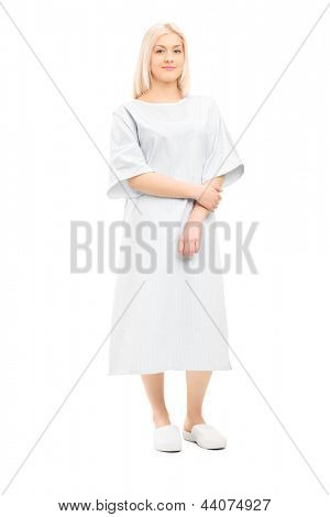 Full length portrait of a female patient posing in a hospital gown, isolated on white background