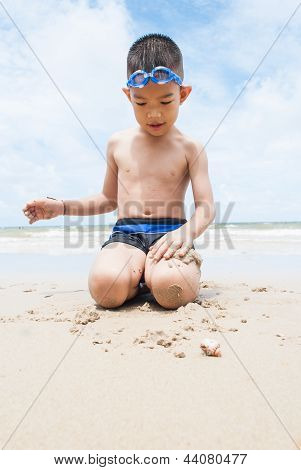 Playful Boy And Hermit Crab On The Beach With Sea  On Background
