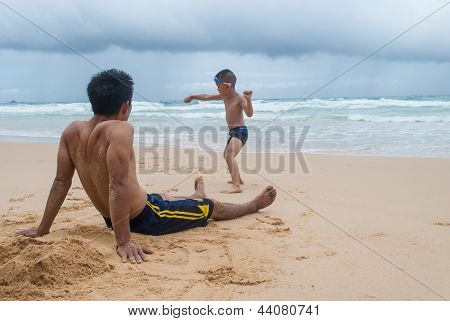 Father And Son Wearing Swimwear Playing On Sandy Beach At Phuket Island,thailand