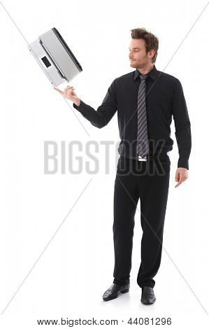 Young businessman balancing a laptop on his forefinger.
