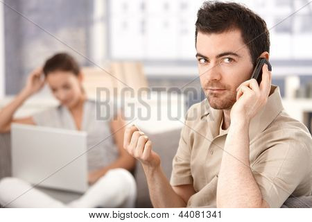 Young man sitting on sofa at home, talking on mobile, woman using laptop in the background.
