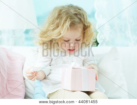 Close-up of a cute girl unwrapping her birthday present