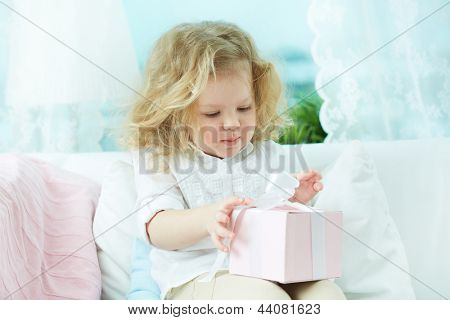 Adorable child unwrapping a birthday gift at home