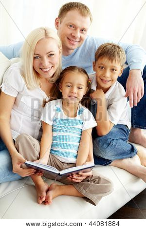 Portrait of happy family looking at camera while reading book