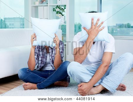 Image of guy and girl sitting on the floor and hiding their faces behind pillows
