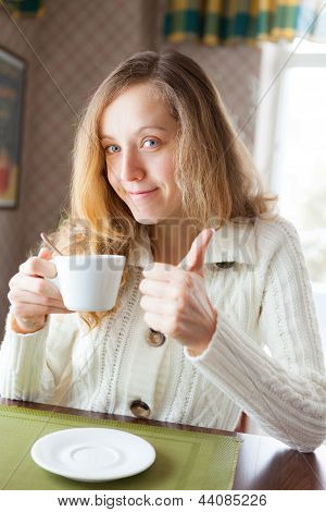 Young Woman With A Cup Of Coffee In Hand Showing Thumb Up Sign