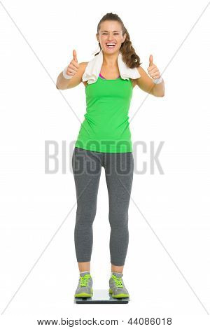 Happy Fitness Young Woman Standing On Scales And Showing Thumbs Up