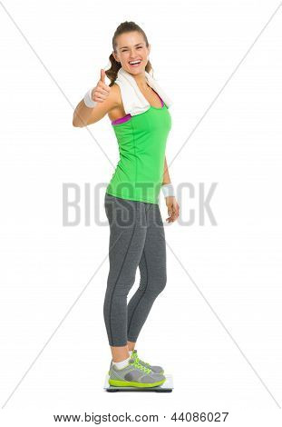 Smiling Fitness Young Woman Standing On Scales And Showing Thumb