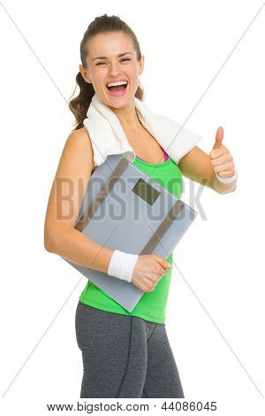 Smiling Fitness Young Woman With Scales Showing Thumbs Up