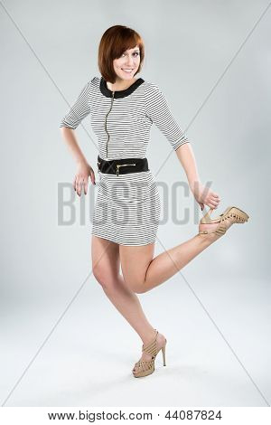 Attractive young brunette woman in a striped dress