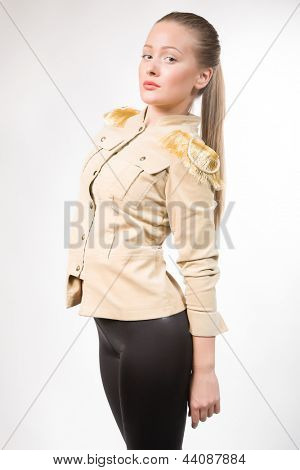 Portrait of the beautiful girl in a jacket with epaulettes.