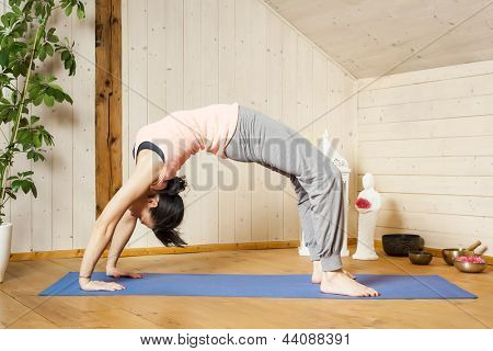 An image of a pretty woman doing yoga at home - Urdhva Dhanurasana