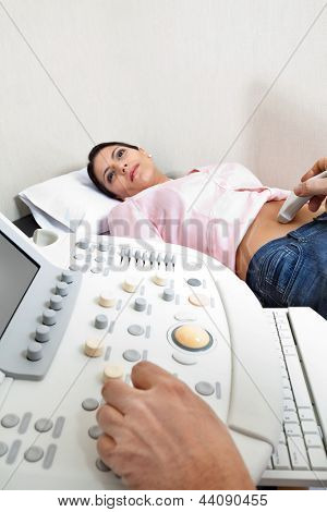 Mid adult female going through an abdomen ultrasound at clinic