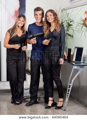 Portrait of confident hairstyling team standing together at beauty parlor