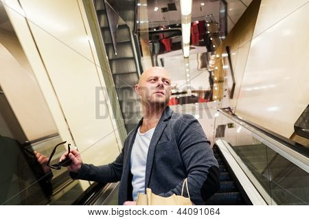 Middle-aged man with shopping bag on an escalator in shopping mall