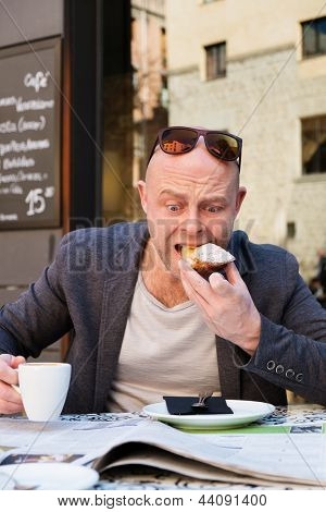 Surprised middle-aged man reading newspaper behind table in street cafe during coffee pause