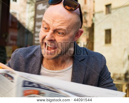 MIddle-aged man becoming enraged while reading newspaper outdoors