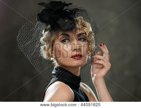 Elegant blond retro woman with red lipstick wearing little hat with veil