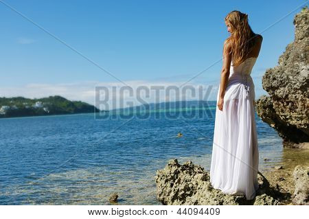 outdoor portrait of young beautiful woman bride in wedding dress on beach
