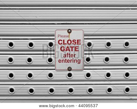 please close sign on a light grey painted perforated roll up gates background