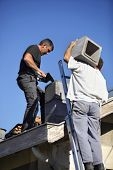 foto of top-less  - Two roofers hard at work - JPG