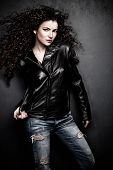 attractive long hair young woman in black leather jacket and blue jeans studio shot small amount of