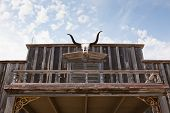 pic of texas-longhorn  - The skull of a Texas longhorn cow is hung above an entrance way of an old western wooden building - JPG