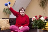 stock photo of physically handicapped  - Mentally disabled woman shows her strength with a dumbbell - JPG
