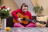 stock photo of physically handicapped  - Mentally disabled woman playing guitar on a couch - JPG