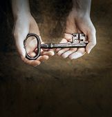 pic of skeleton key  - Man holding a big old antique skeleton key in his hands - JPG