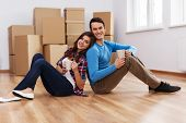 stock photo of heterosexual couple  - Young couple sitting on the floor in their new home - JPG