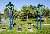 picture of swingset  - Blue swingset on playground in a park - JPG