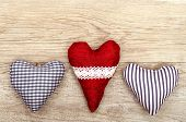 stock photo of bordure  - Three hearts of cloth on old wooden board - JPG