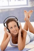 Pretty girl listening to music, using headphones, laying on floor at home, smiling.