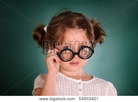 Little girl with thick bottle glasses on green background