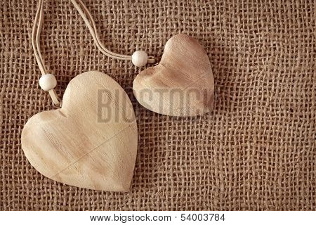 Two wooden hearts on fabric background