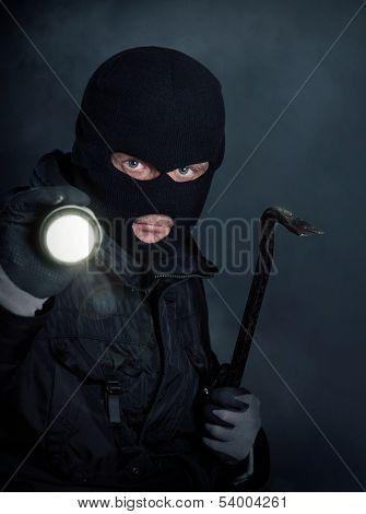 Burglar in black balaclava with crowbar and flashlight at night